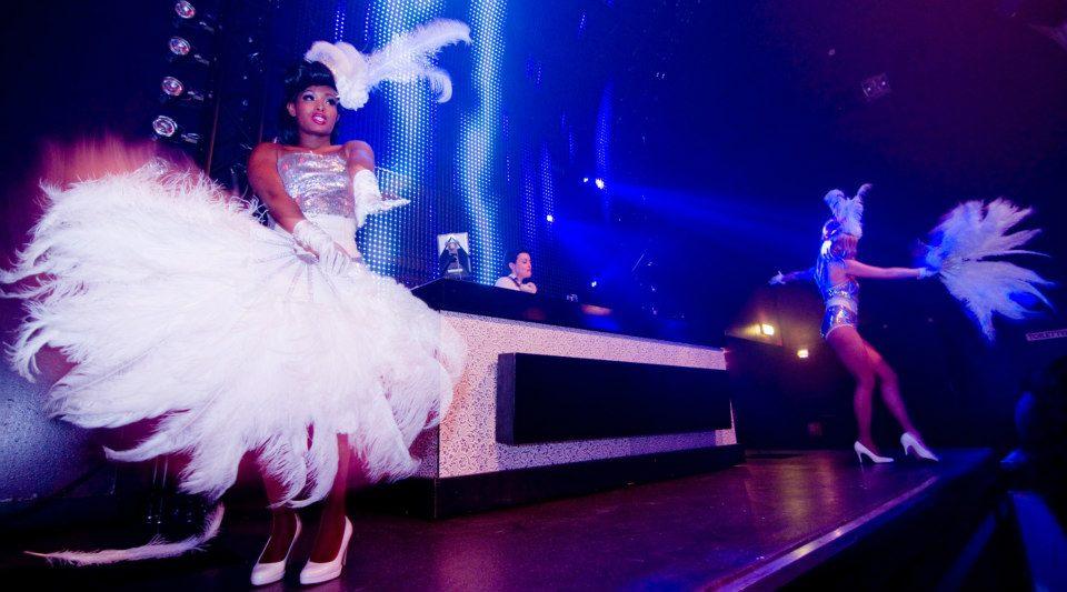 Gatsby Party DJ met danseressen met grote veren waaier op podium
