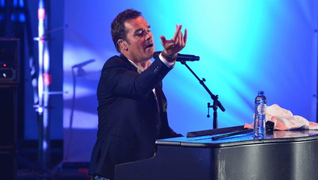 Jeroen van der Boom zingend achter piano