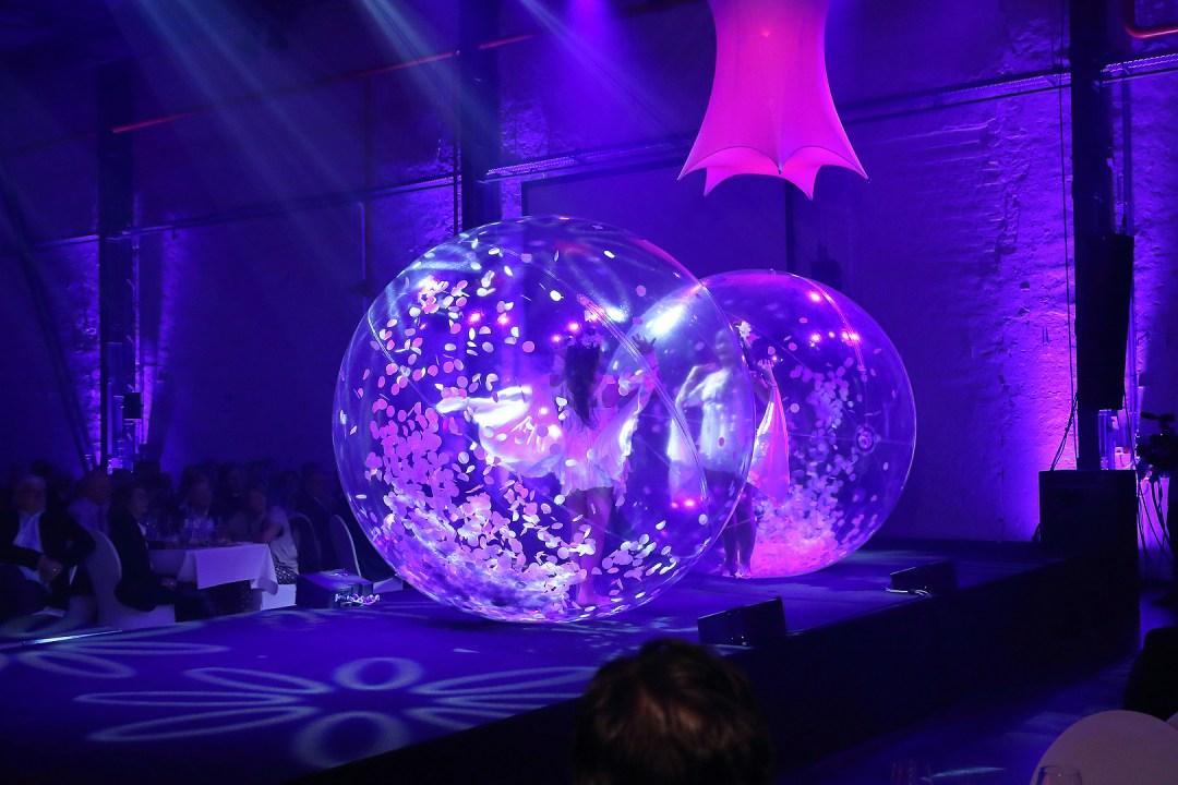 Twee Transparante ballen met danseres op catwalk