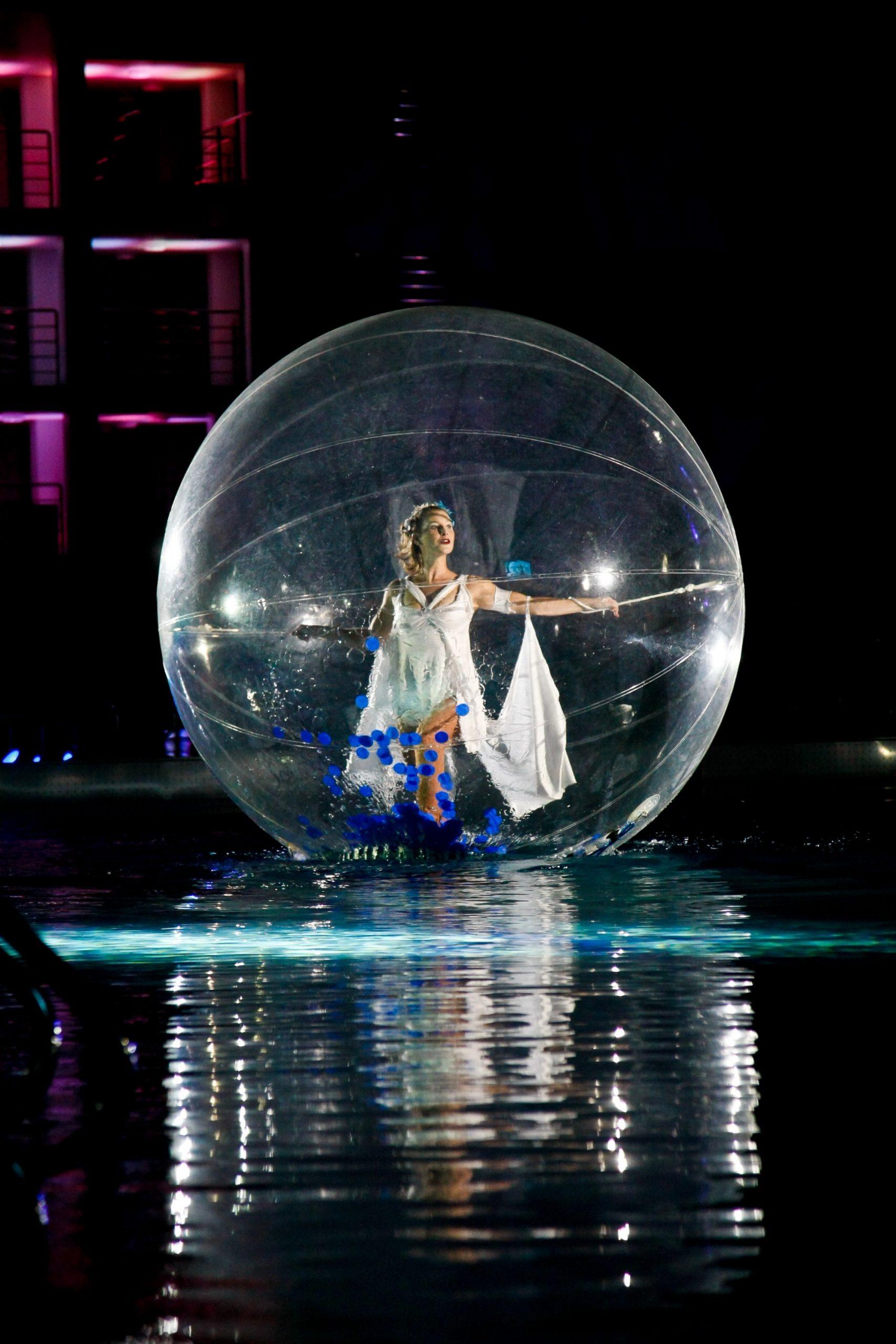 Transparante bal met danseres op water